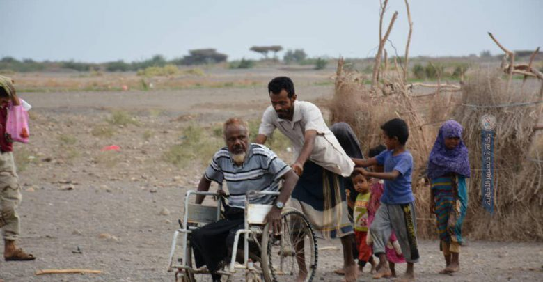 Aish on his old shabby wheelchair as his son helps him with it